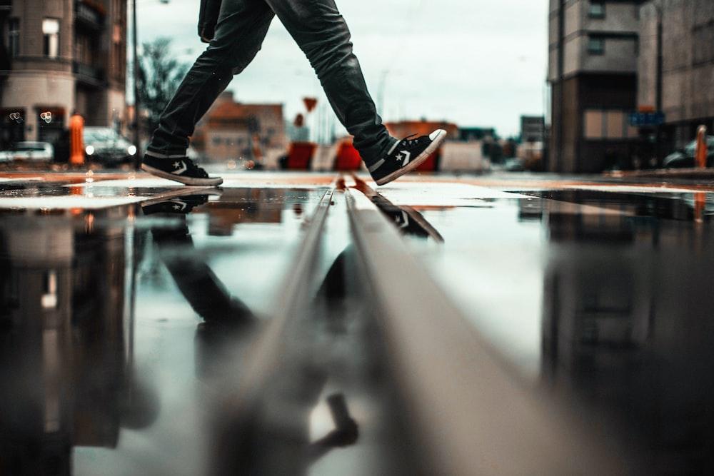 person walking in wet road