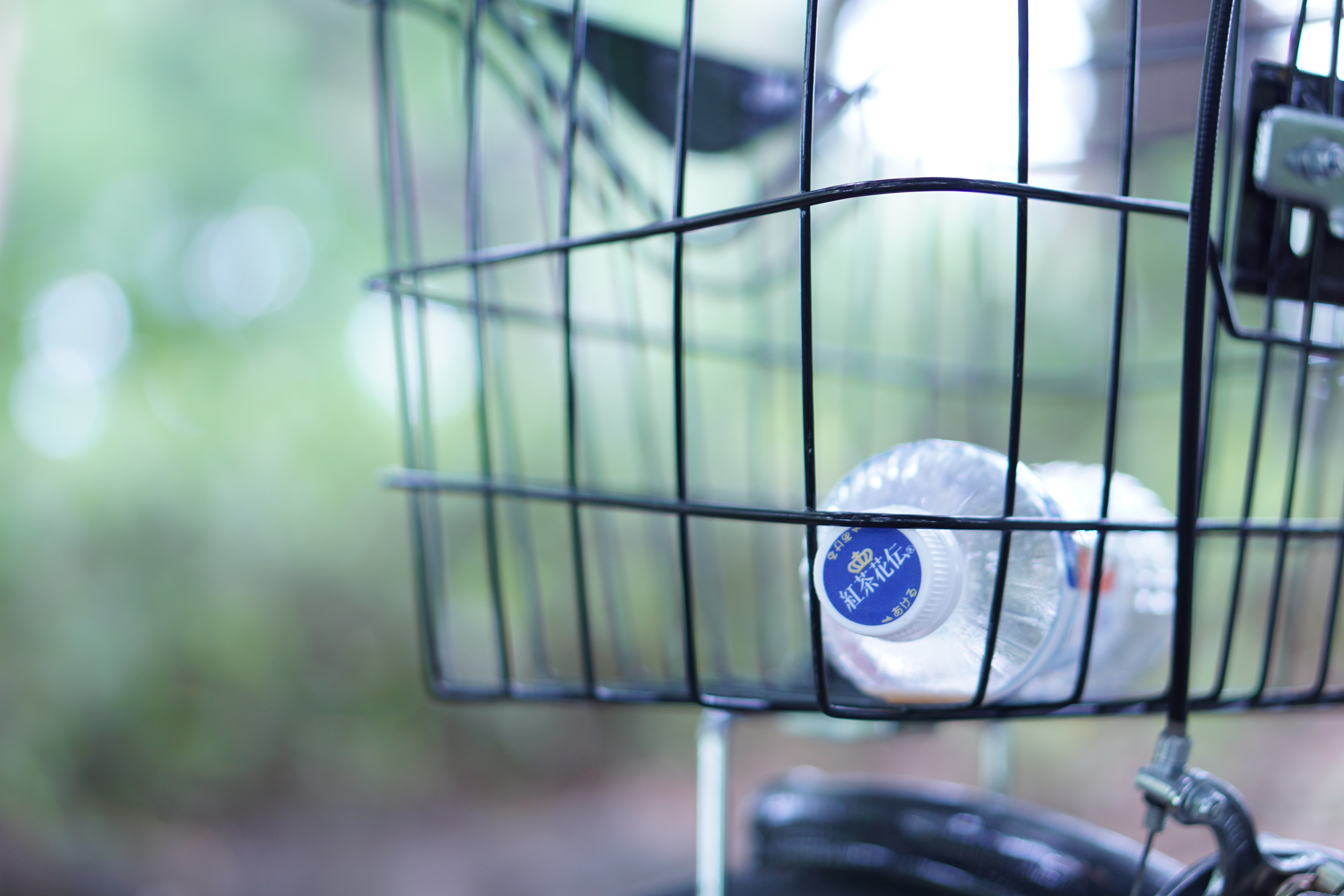 clear plastic bottle in black bicycle basket