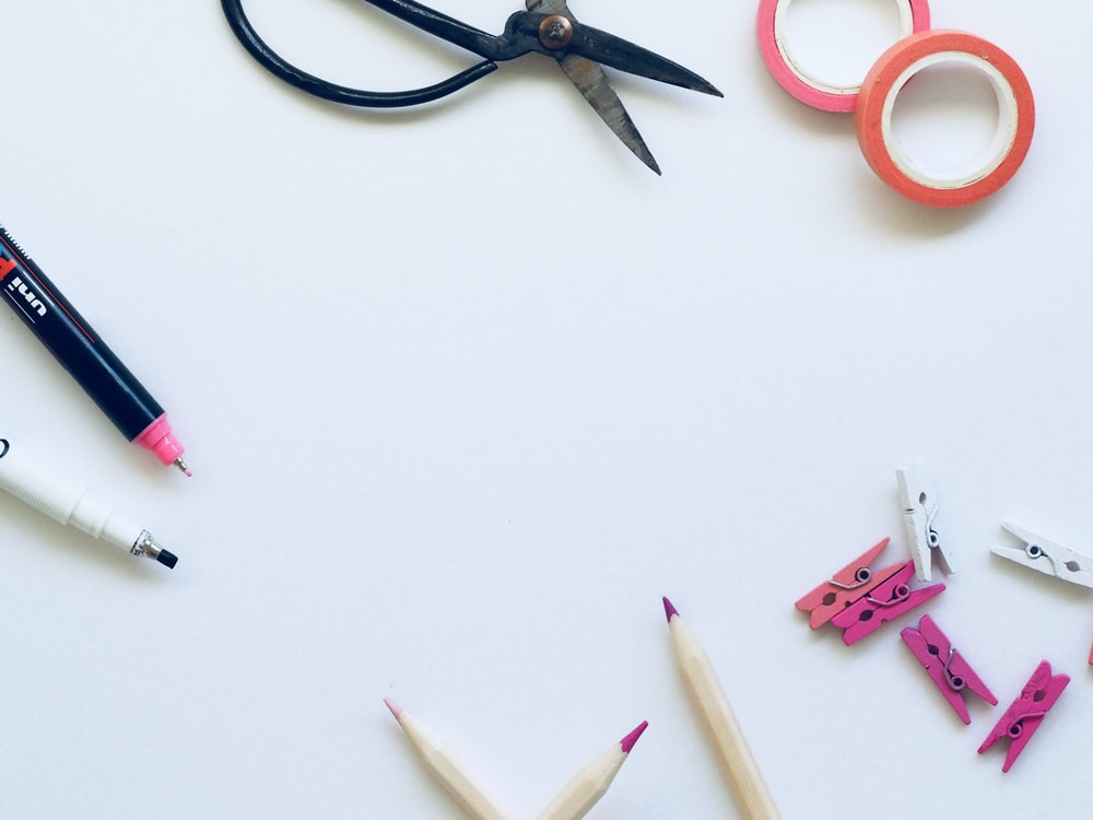 black scissors near brown pencils on top of white textile