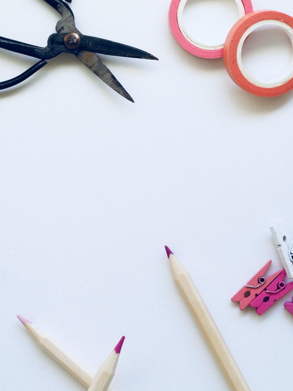 three pens beside scissors