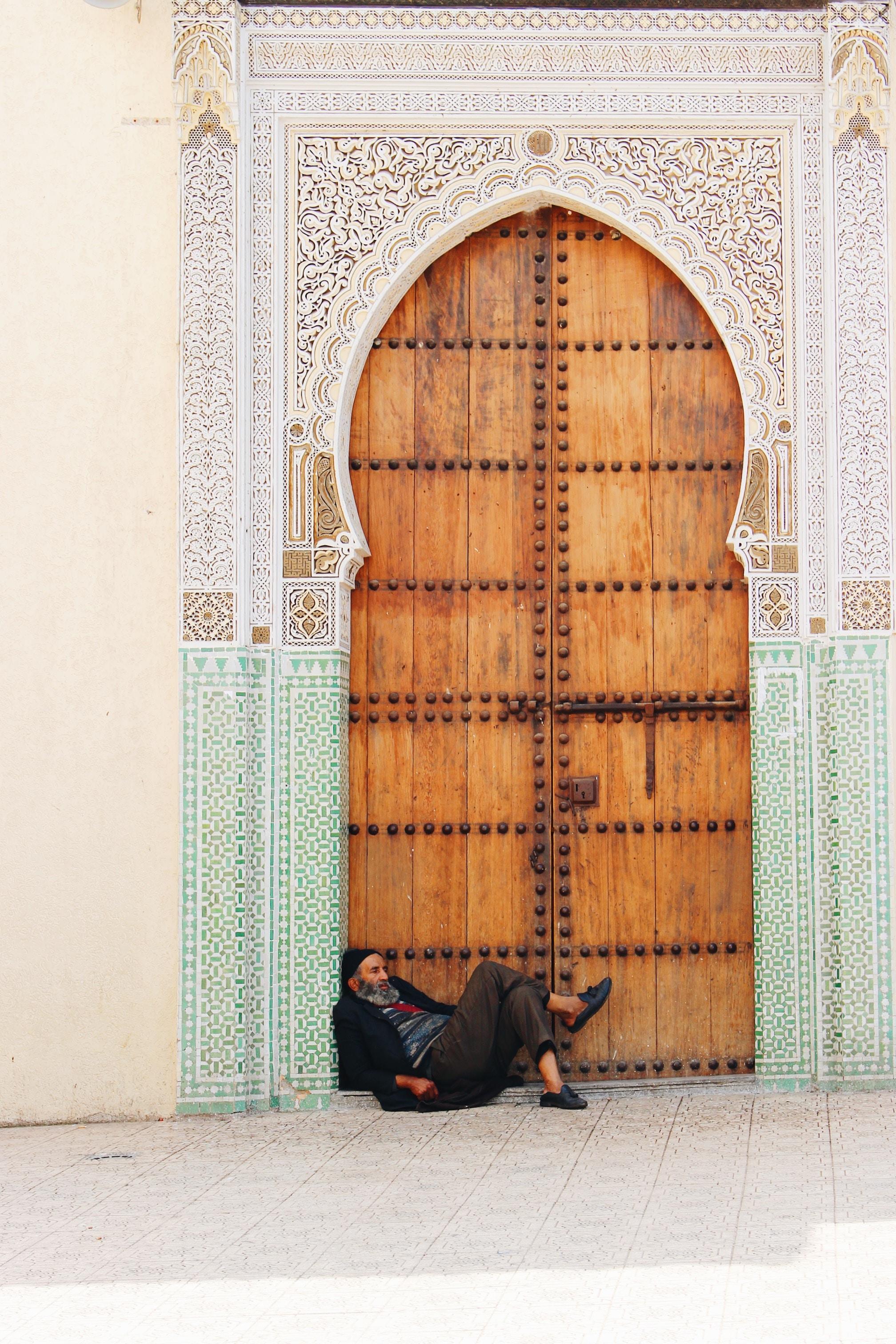 man in black pants sitting beside door