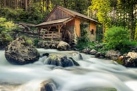 brown wooden house with water mill