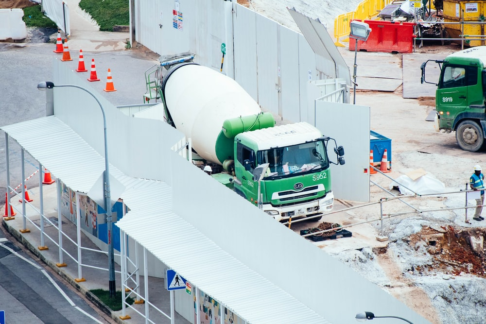 green and white mixer truck at the construction site