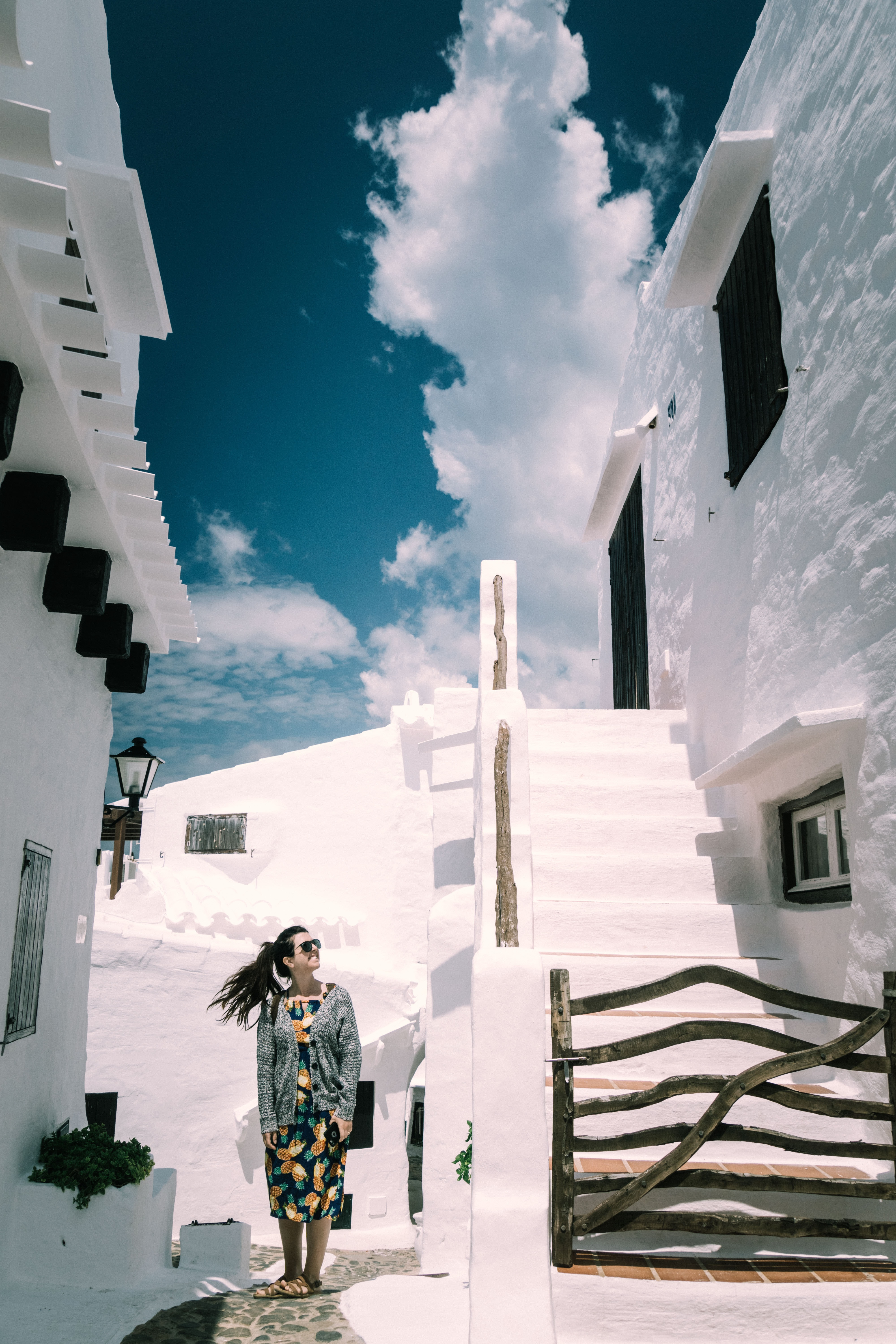 woman standing near white building and stairs