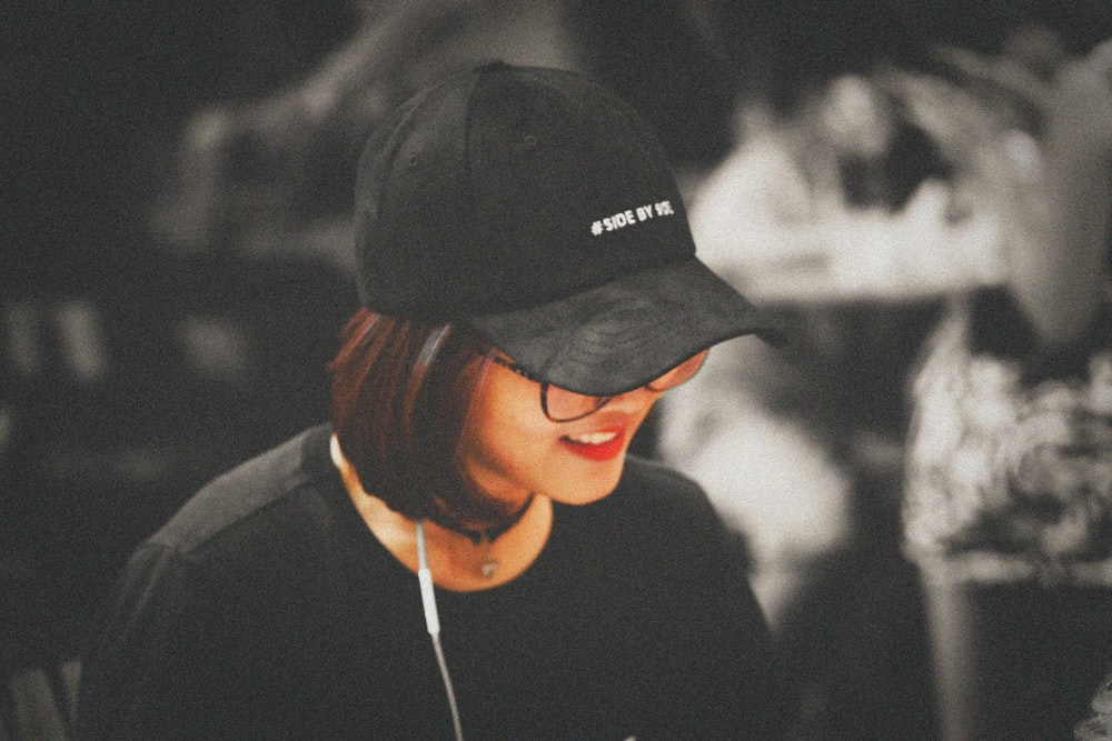 selective color photography of woman wearing black fitted cap