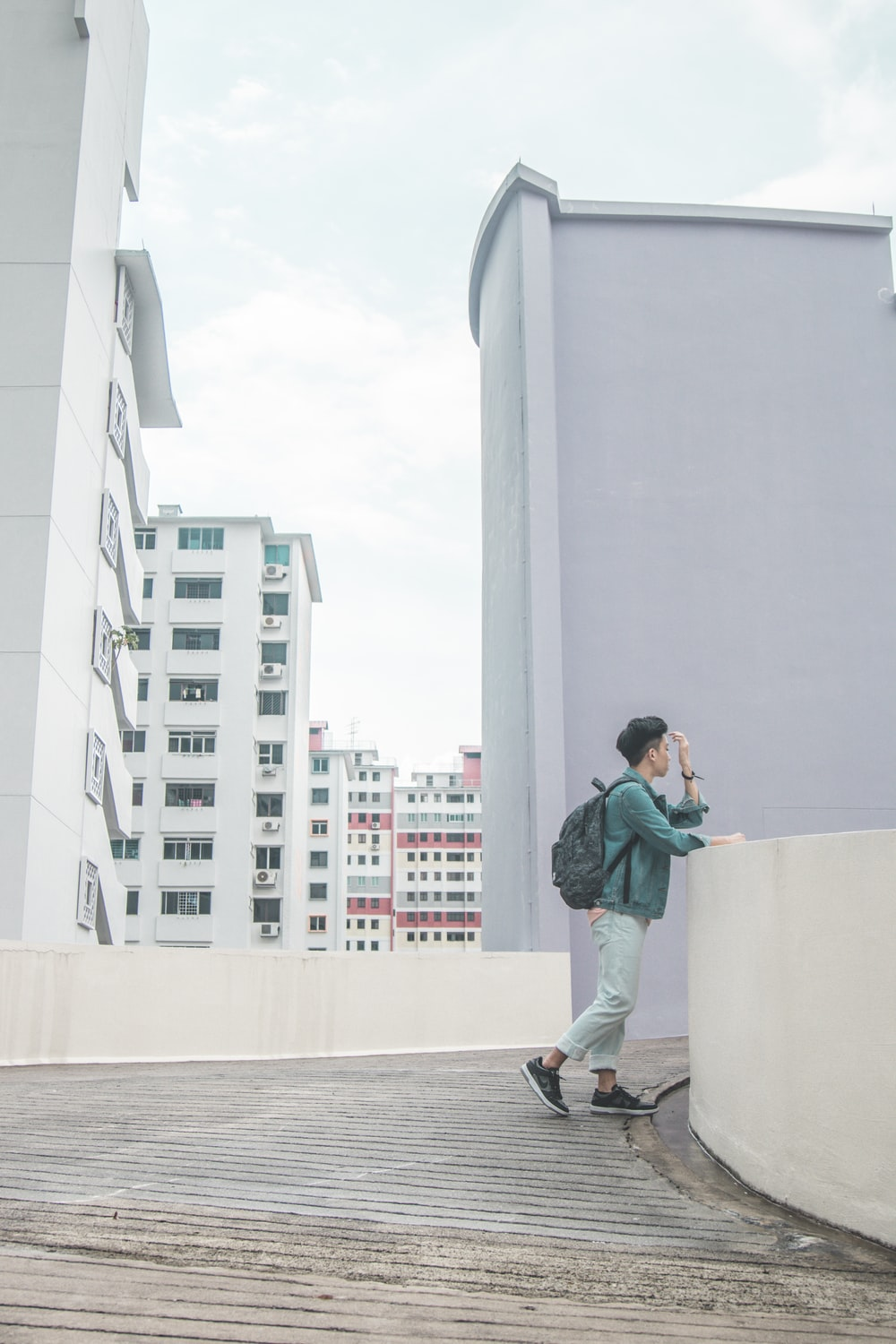 man in teal jacket standing beside white concrete fence