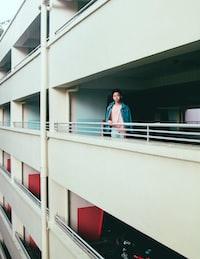 man wearing pink shirt standing near balcony