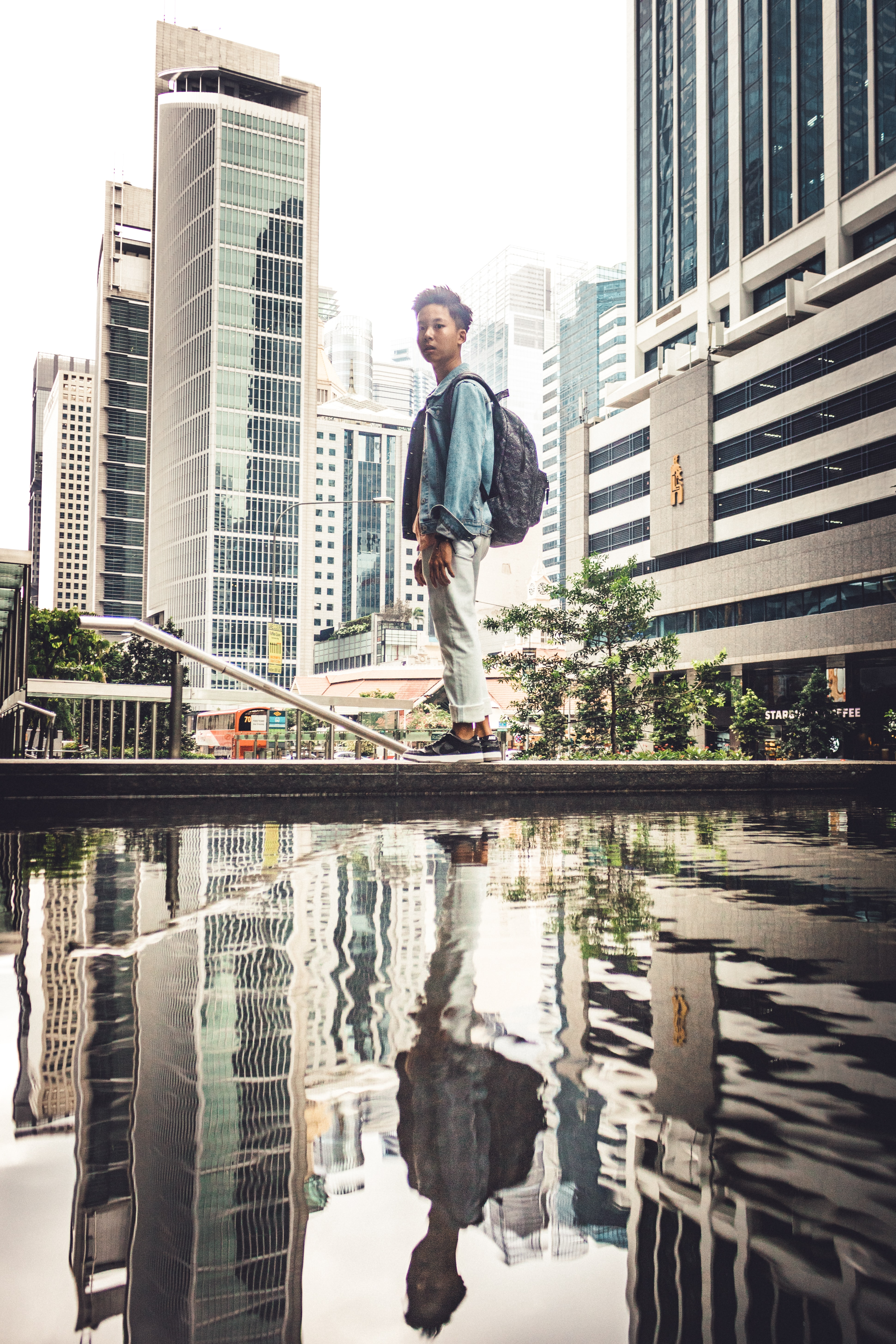 man standing on fountain edge near city buildings during daytime
