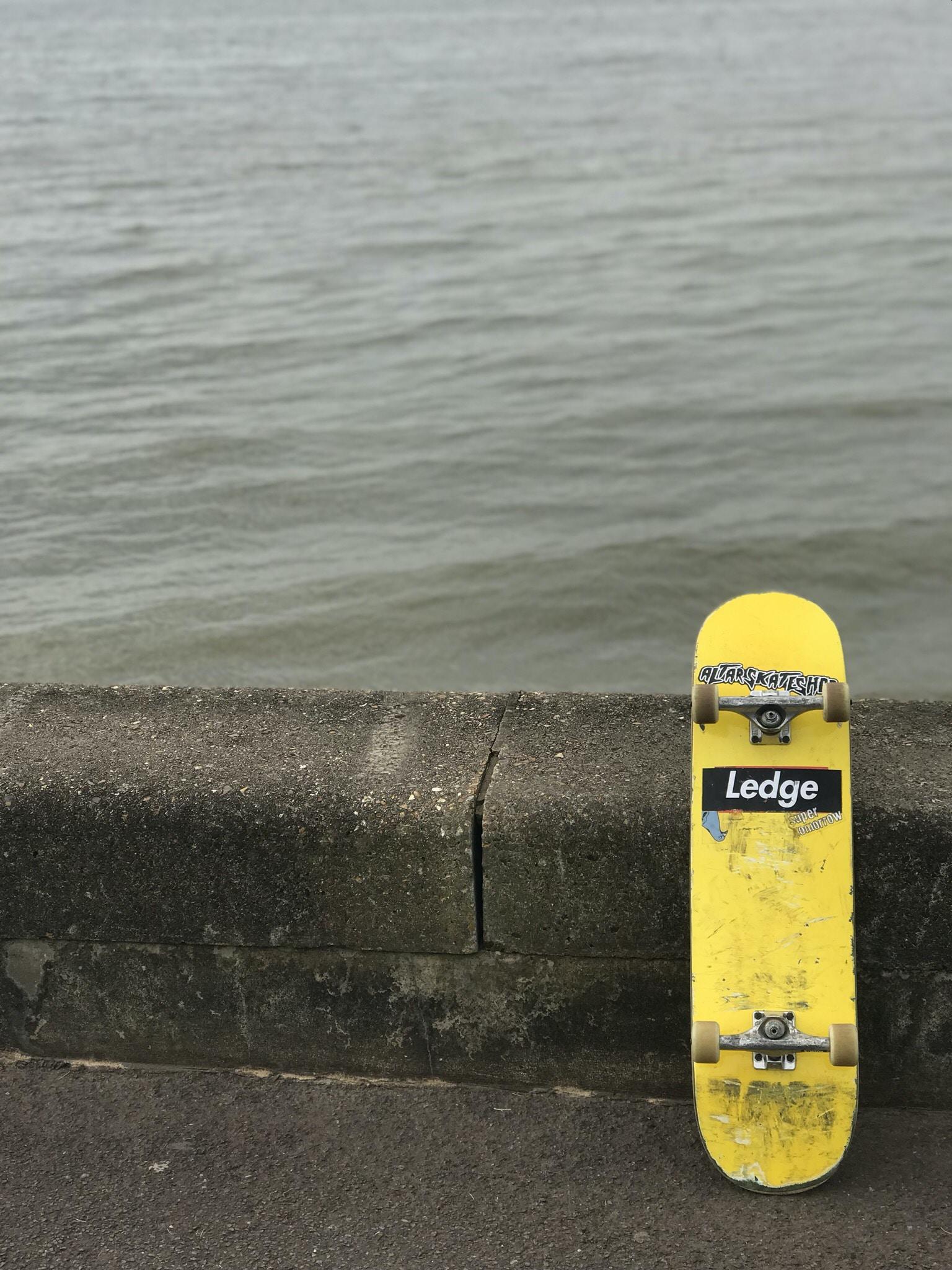 yellow Ledge skateboard near body of water