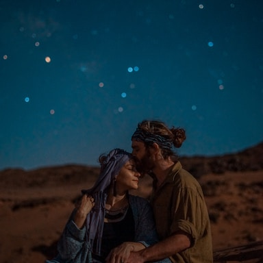 man and woman sitting on desert sand under blue sky during nighttime