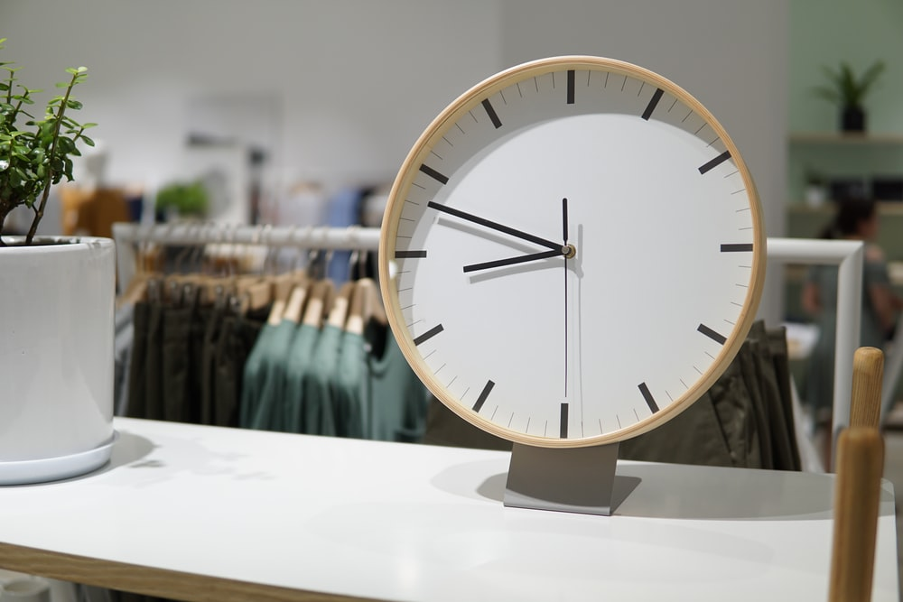 brown and white wall clock displaying 8:44
