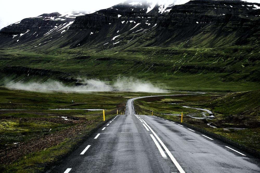 grey concrete road going trough moutain