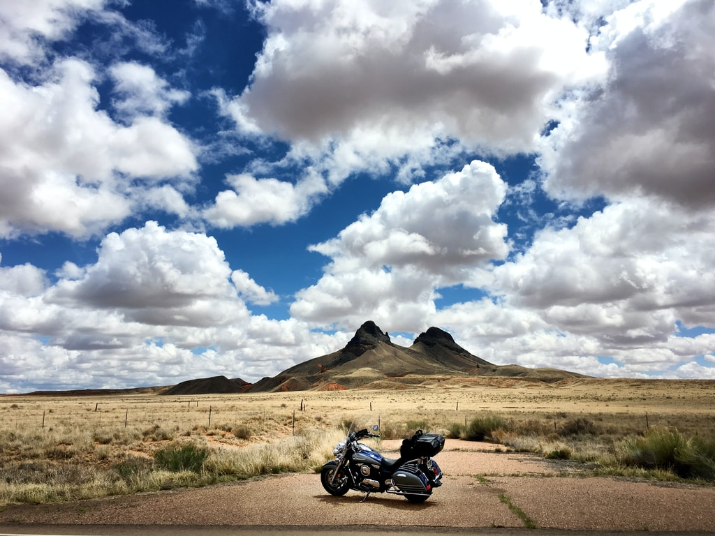 parked touring motorcycle under blue sky during daytime