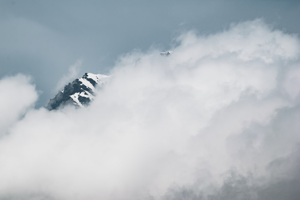 landscape photography of snowy mountain covered white clouds