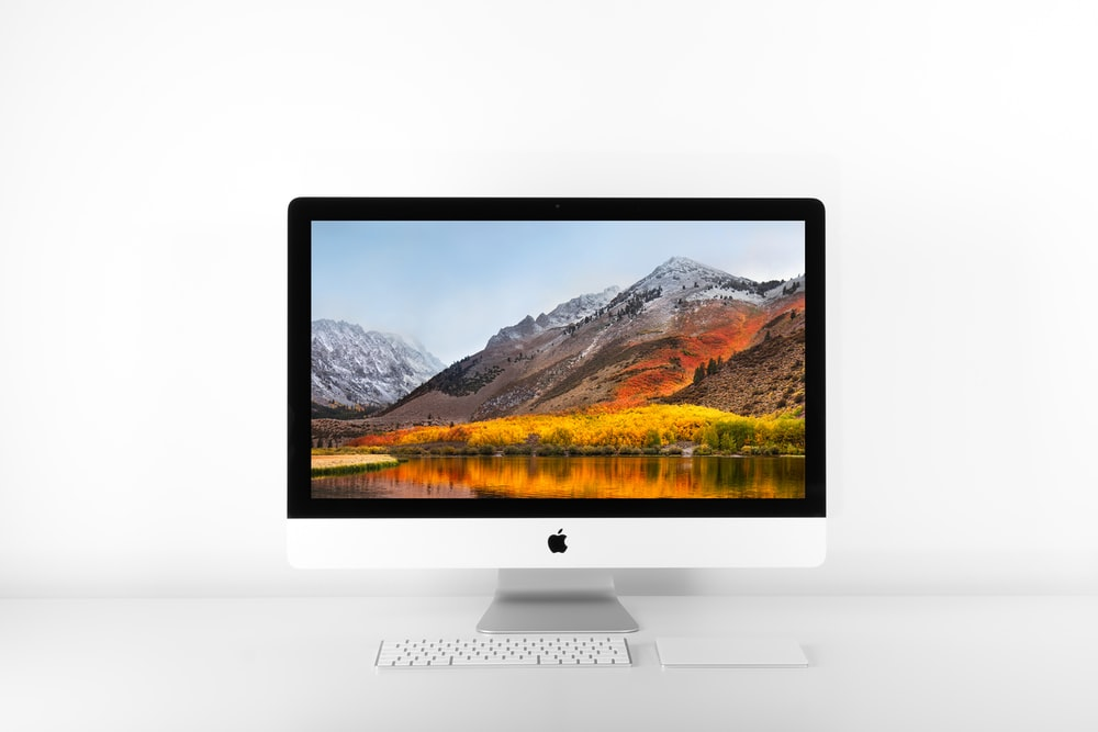 silver iMac and Magic keyboard on white surface
