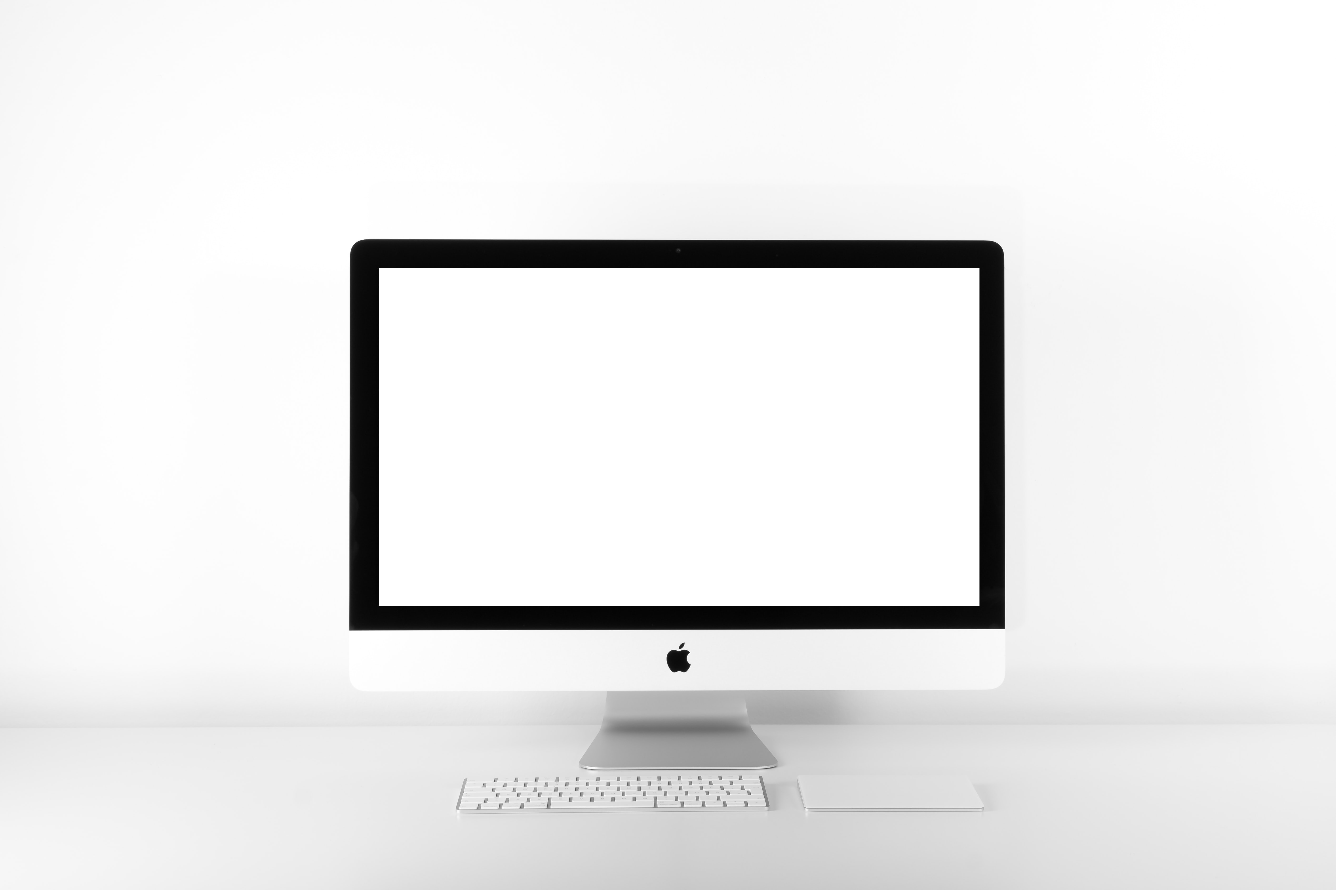 silver iMac with Apple Magic Keyboard on white sufrace