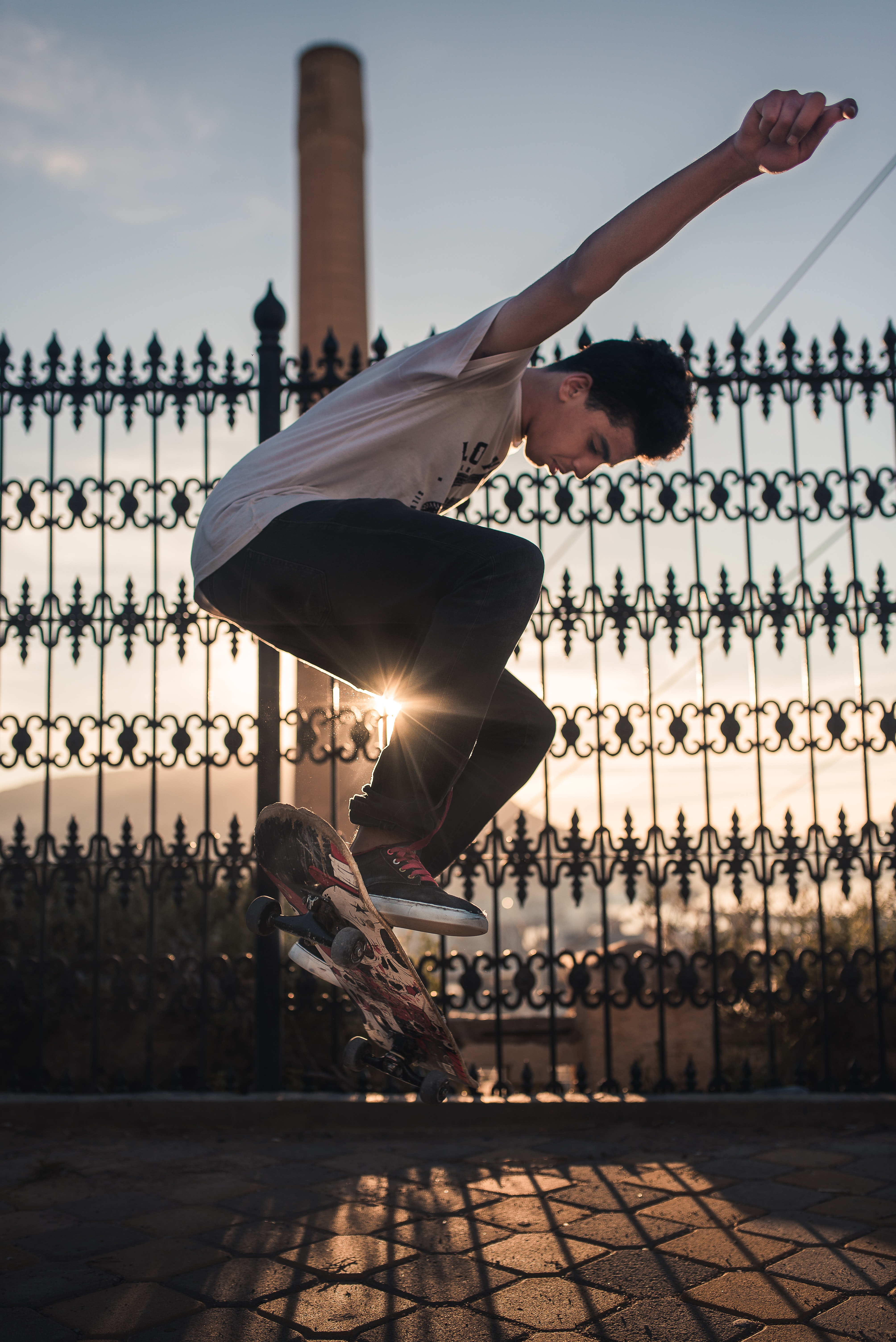 man doing skateboard trick near black steel fence during daytime
