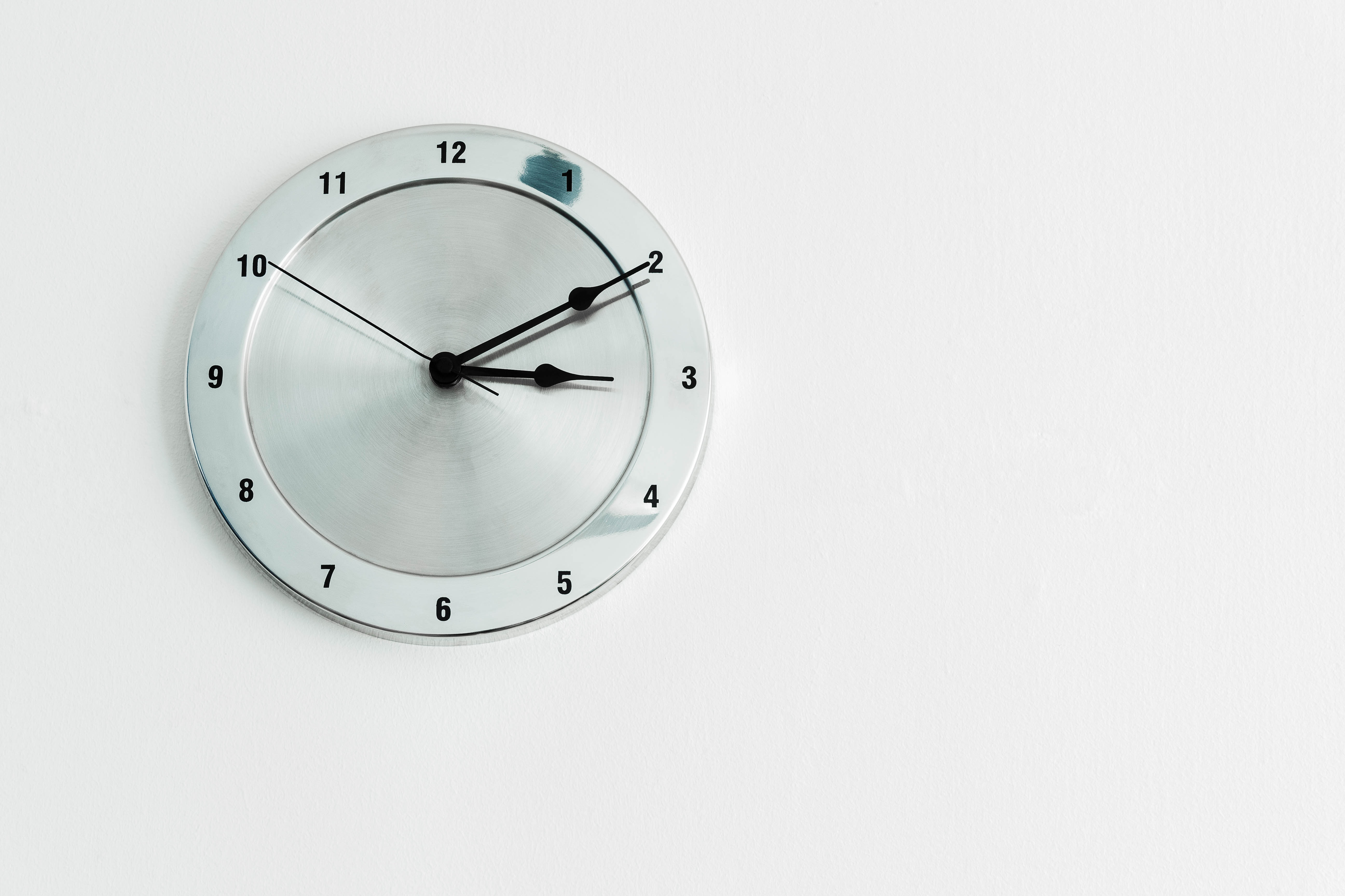 round stainless steel analog wall clock displaying 3:10 time
