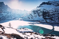 landscape photography of body of water surrounded by snowy mountains