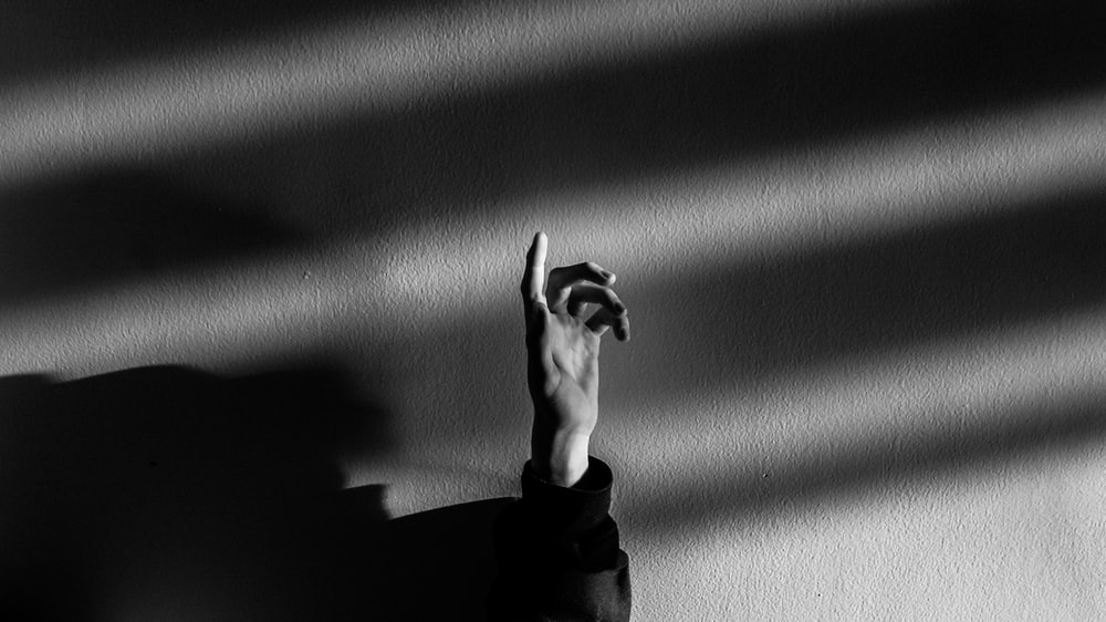 grayscale photography of person raising his hand