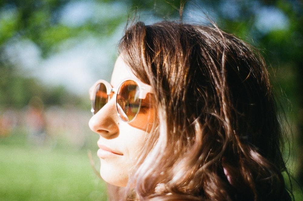 woman closing her eyes wearing brown lens sunglasses
