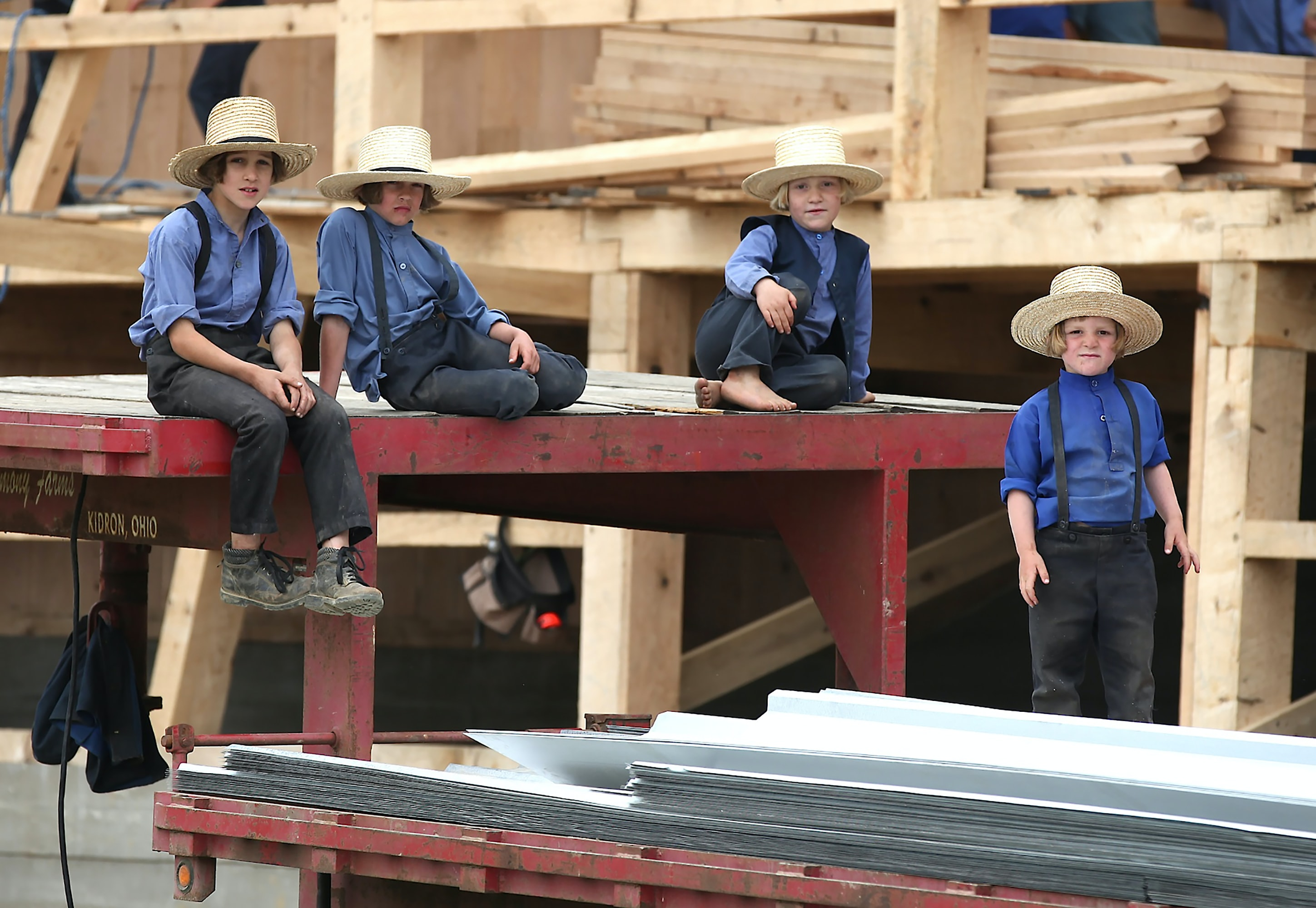 four boys sitting on red steel frame