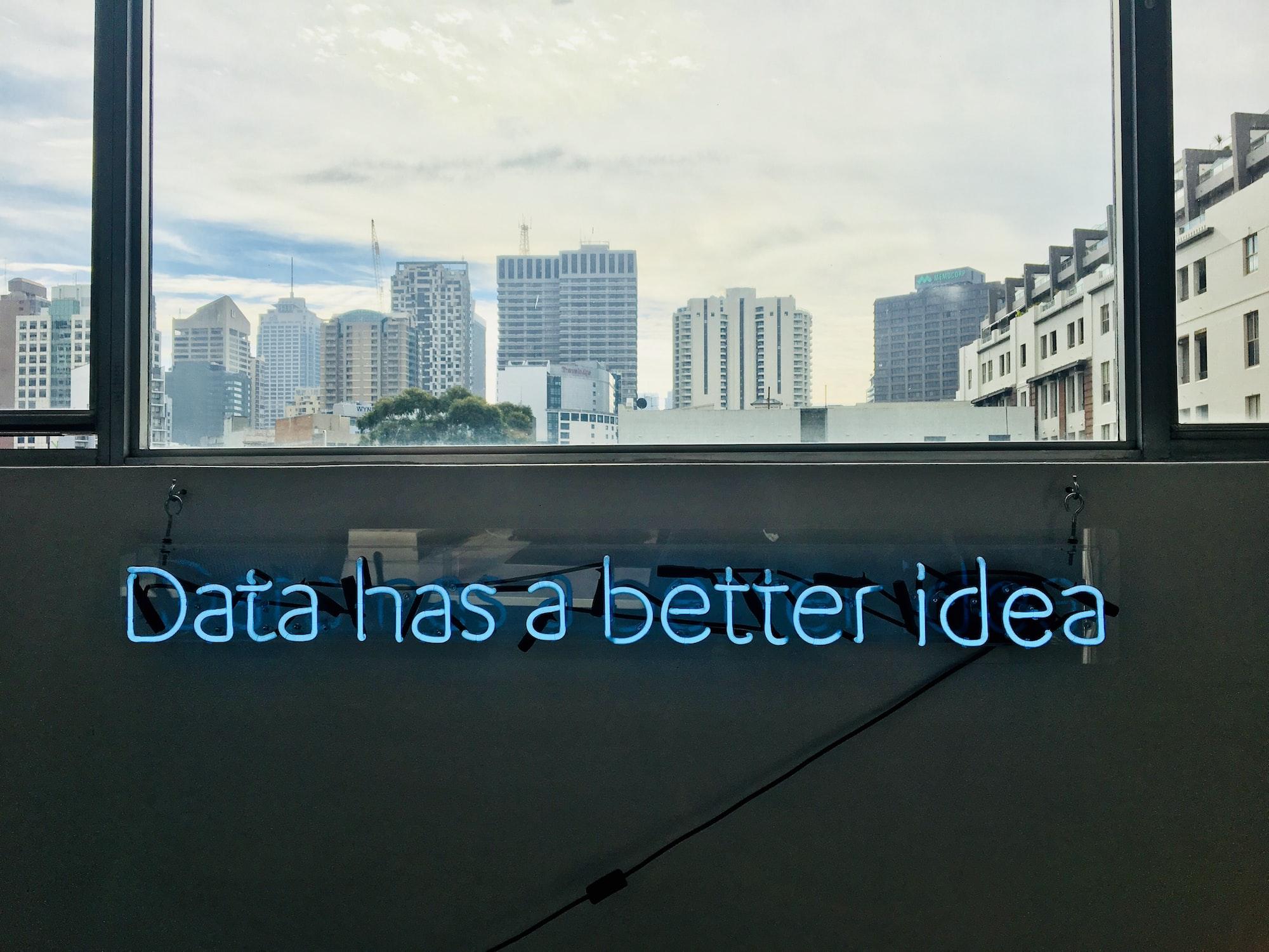 """Frase """"Data has a better idea"""" com letras em led presas numa parede que está embaixo de uma janela mostrando a cidade."""
