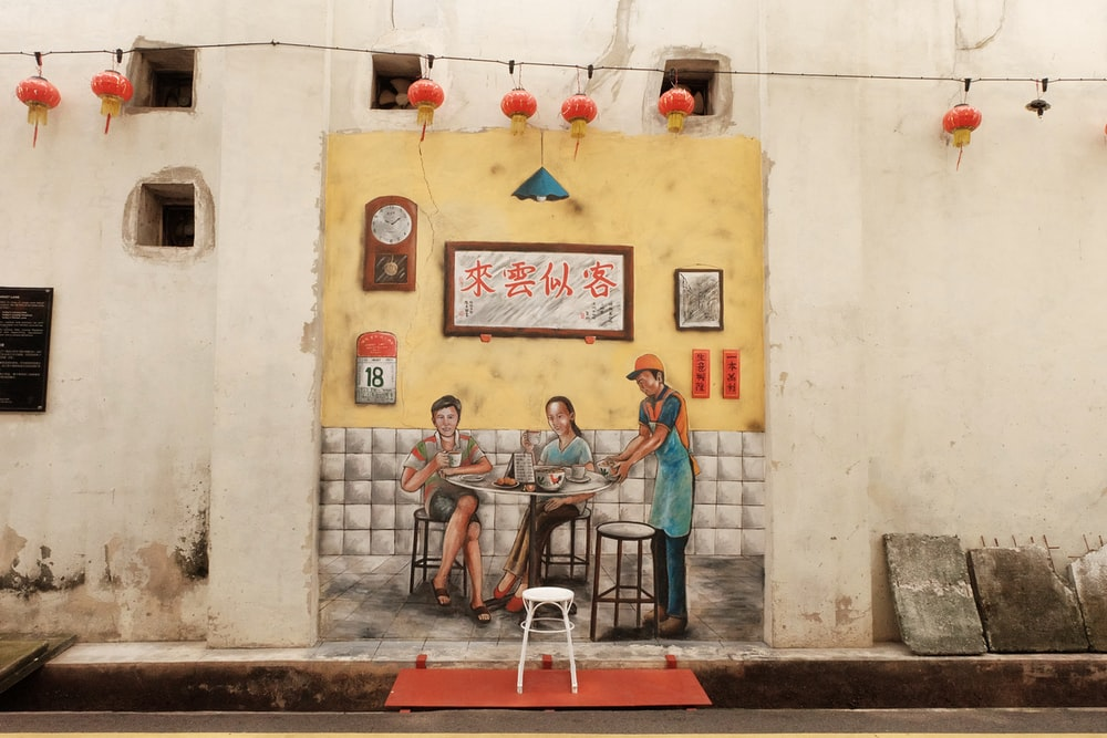 two women sitting while waiter is serving painting