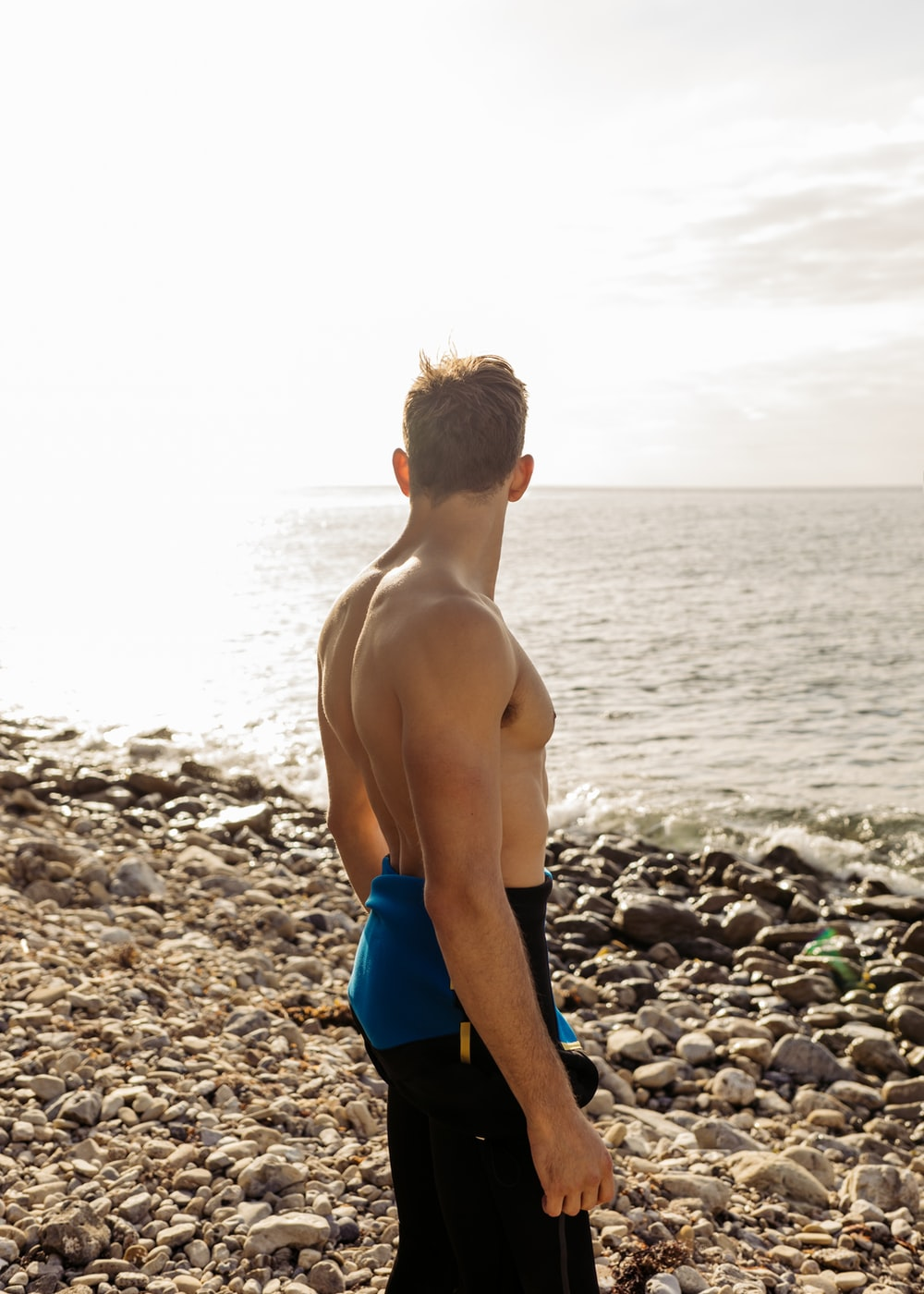 man in blue and black bottoms standing on beach
