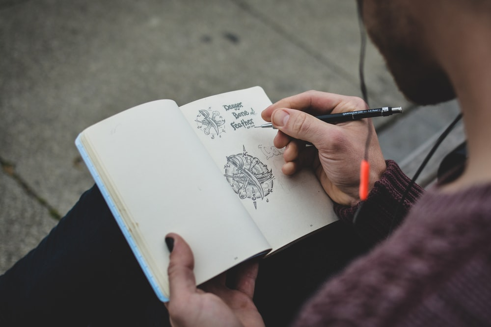 shallow focus photography of person drawing