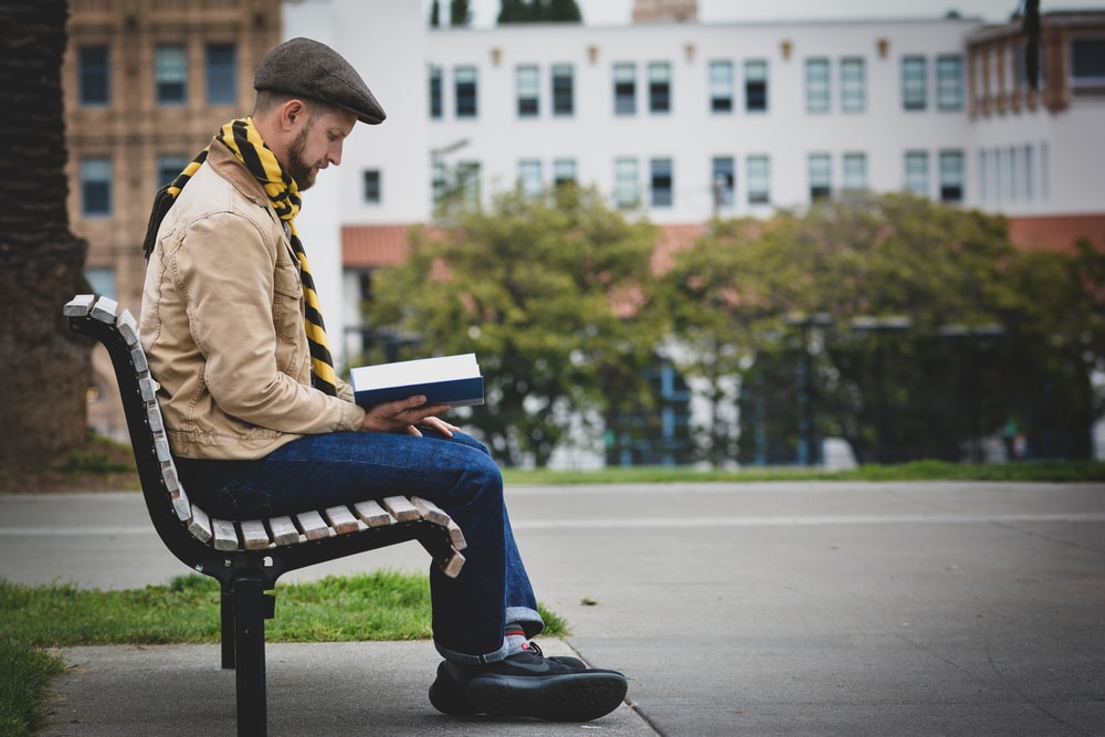 man reading book while sitting on bench outdoors
