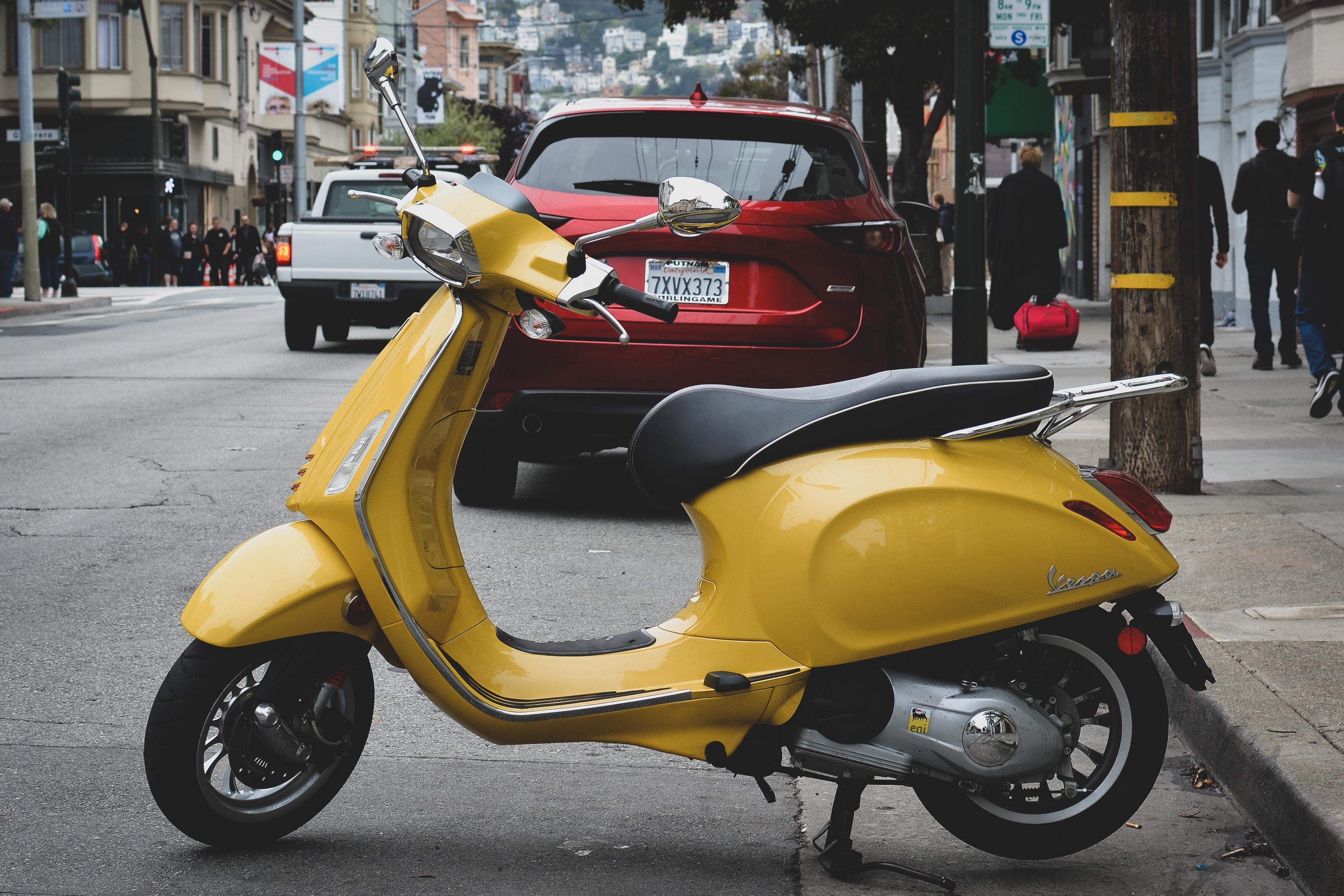 yellow motor scooter parked near sidewalk