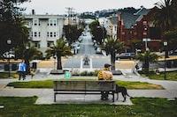 man sitting on bench beside door in park at daytime