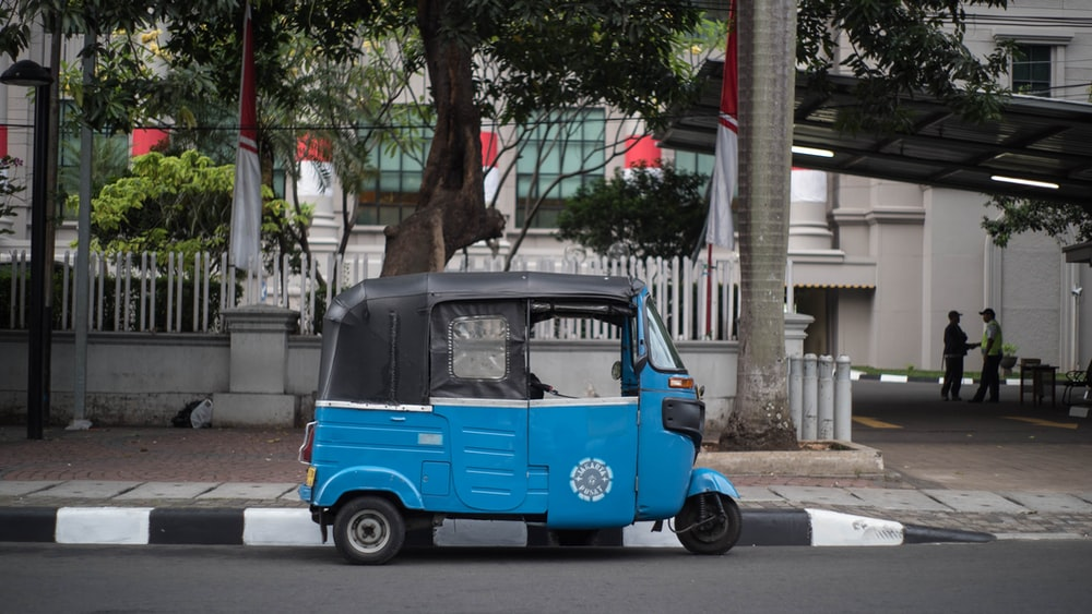 black and blue auto rickshaw on gray concrete road