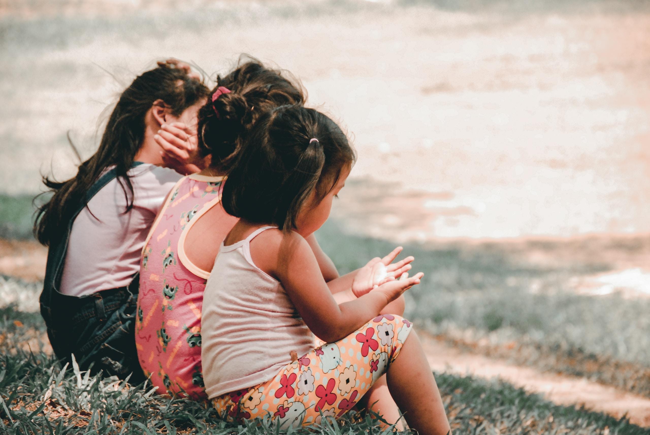 three children sitting on grass