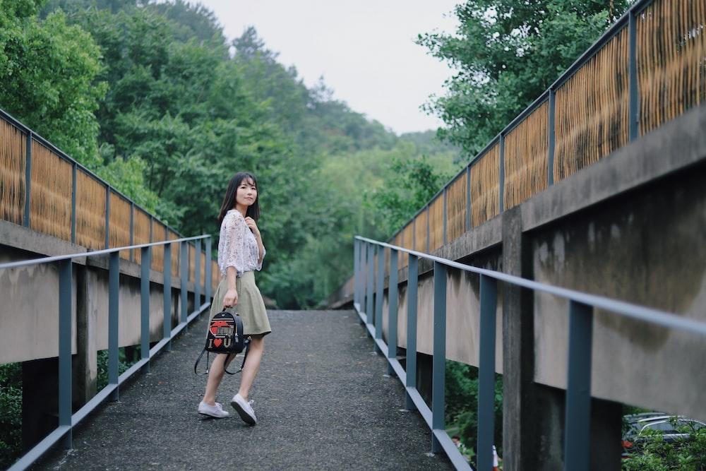 woman standing on walkway holding backpack
