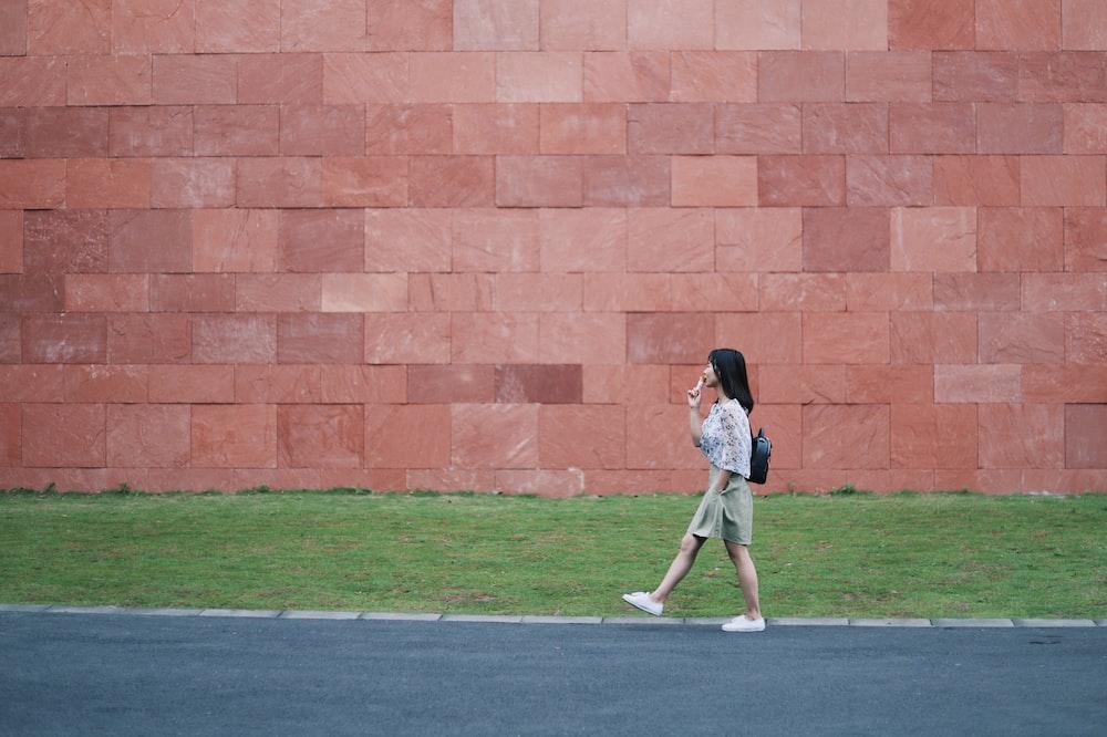 woman walking on asphalt road