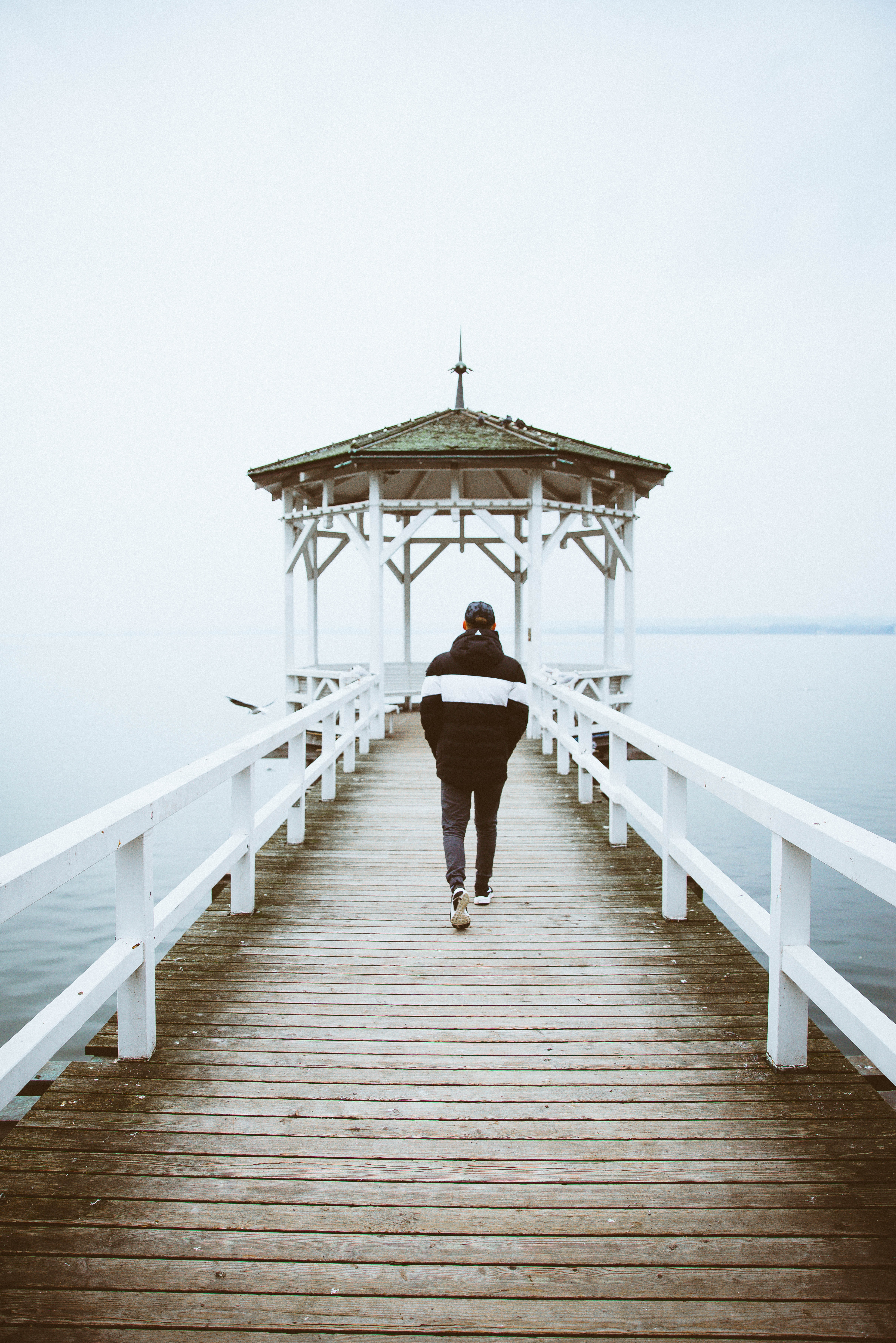 person walking toward cottage on body of water