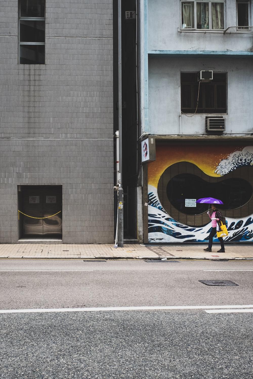 person holding up purple umbrella walking on sidewalk
