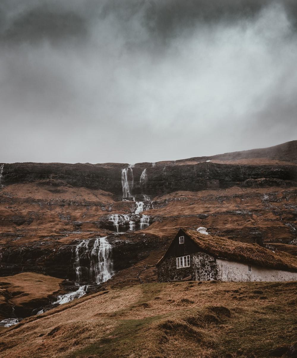 waterfalls near wooden house under gray skies