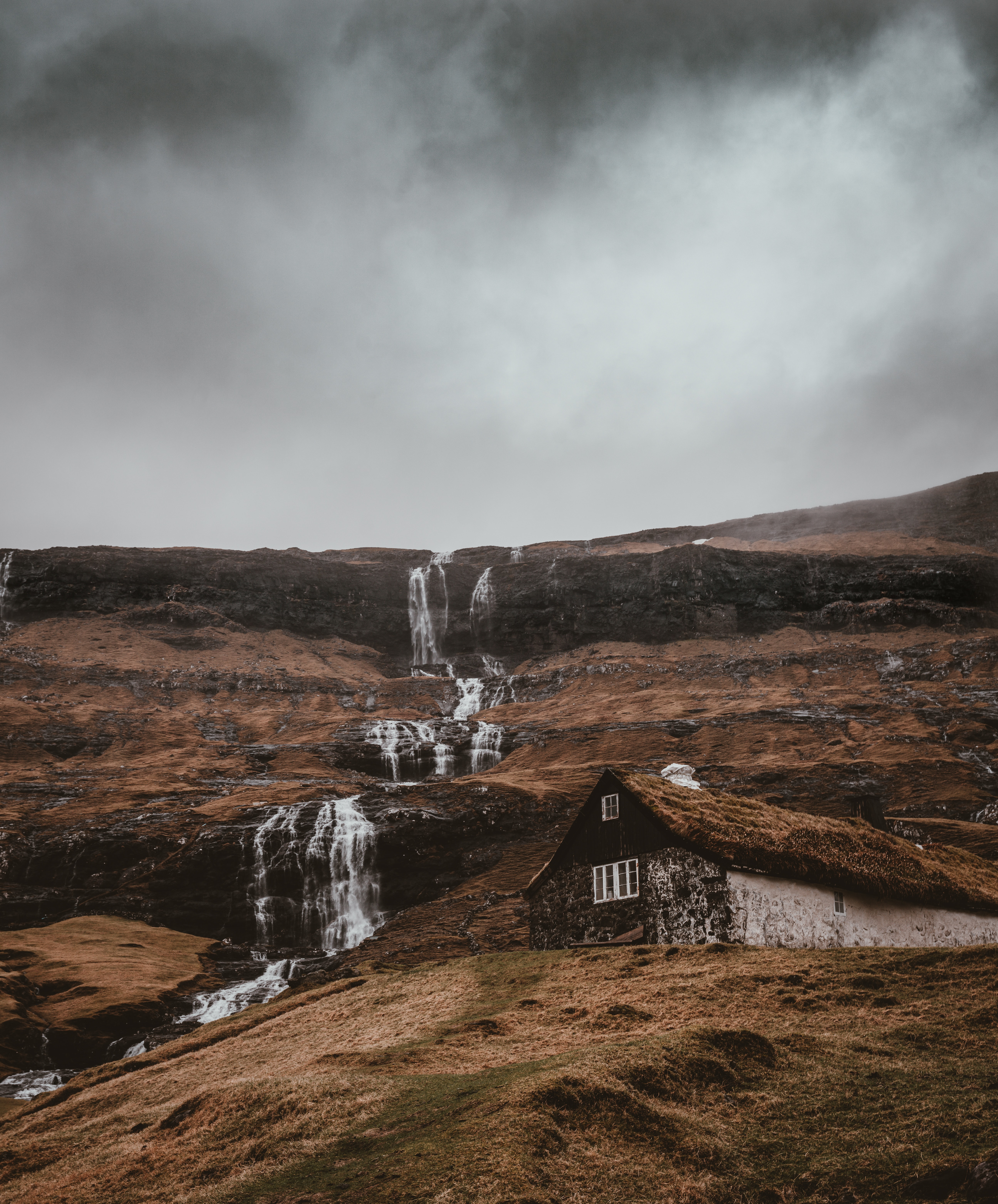 waterfalls near wooden house under gray skies