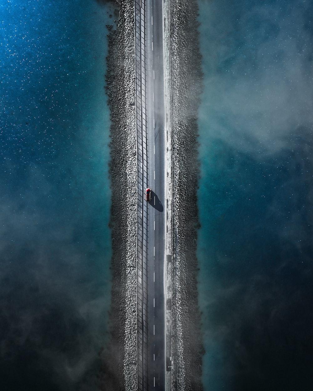 bird's eye view photo of car on asphalt road between body of water