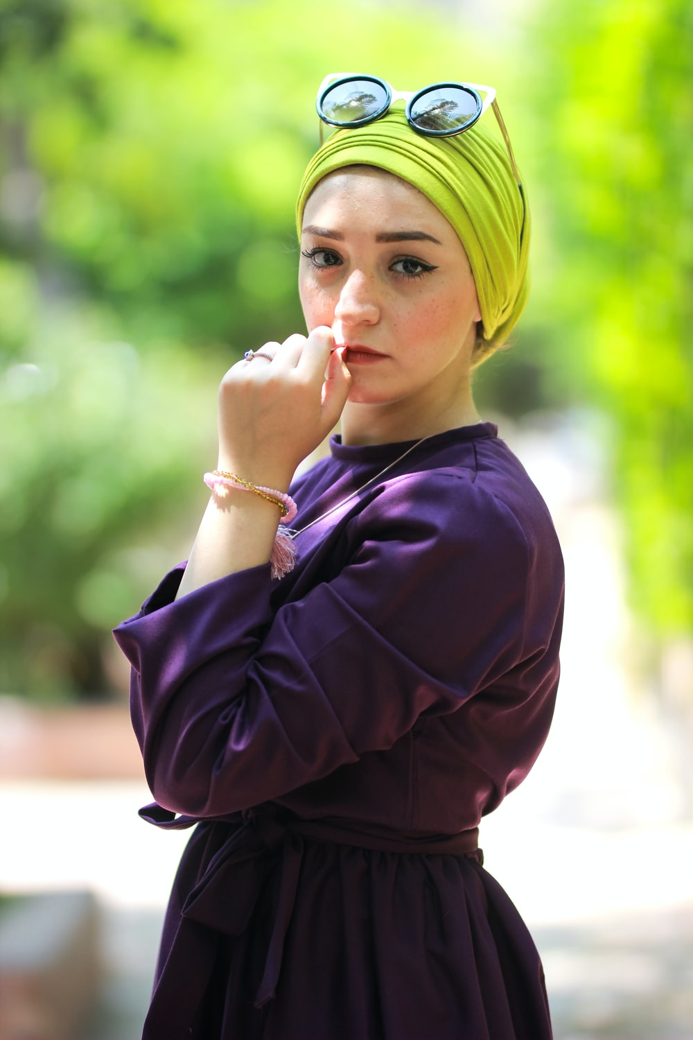 woman wearing purple long-sleeved top holding her lips during daytime