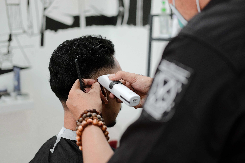 man holding white hair trimmer