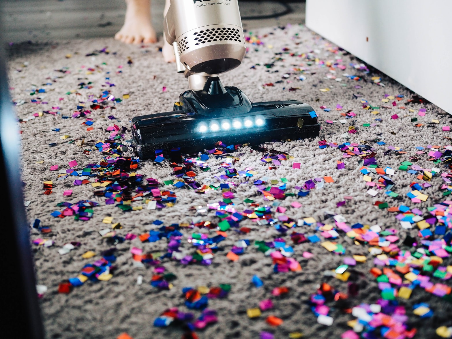 Handheld vacuum cleaning the carpet with full of confetti