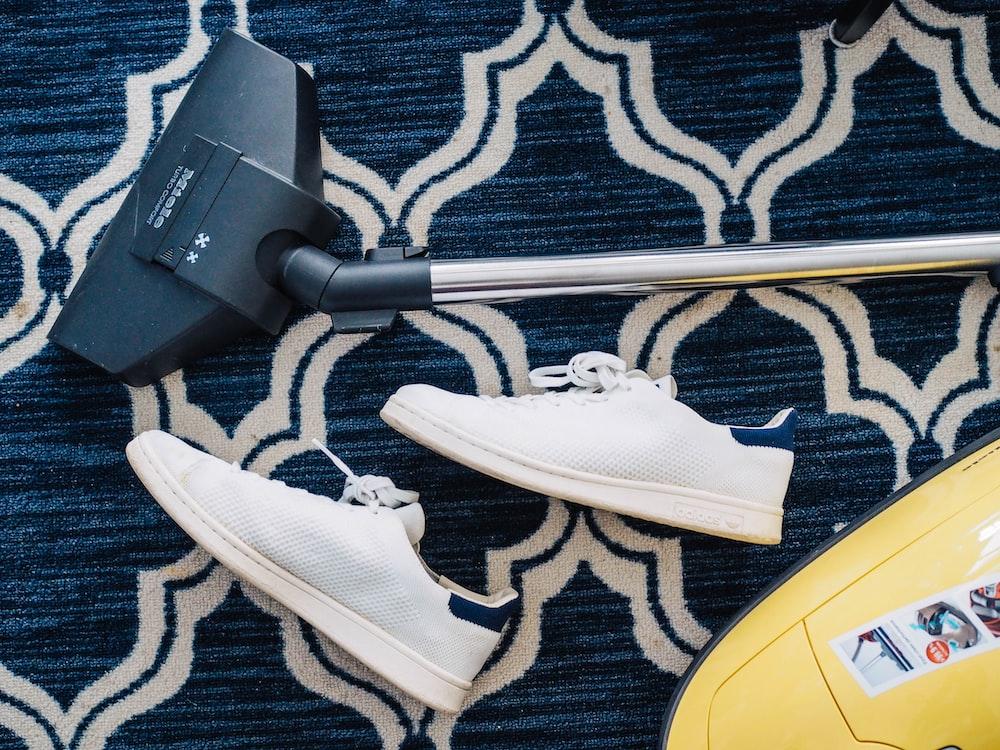 pair of white sneakers beside vacuum cleaner
