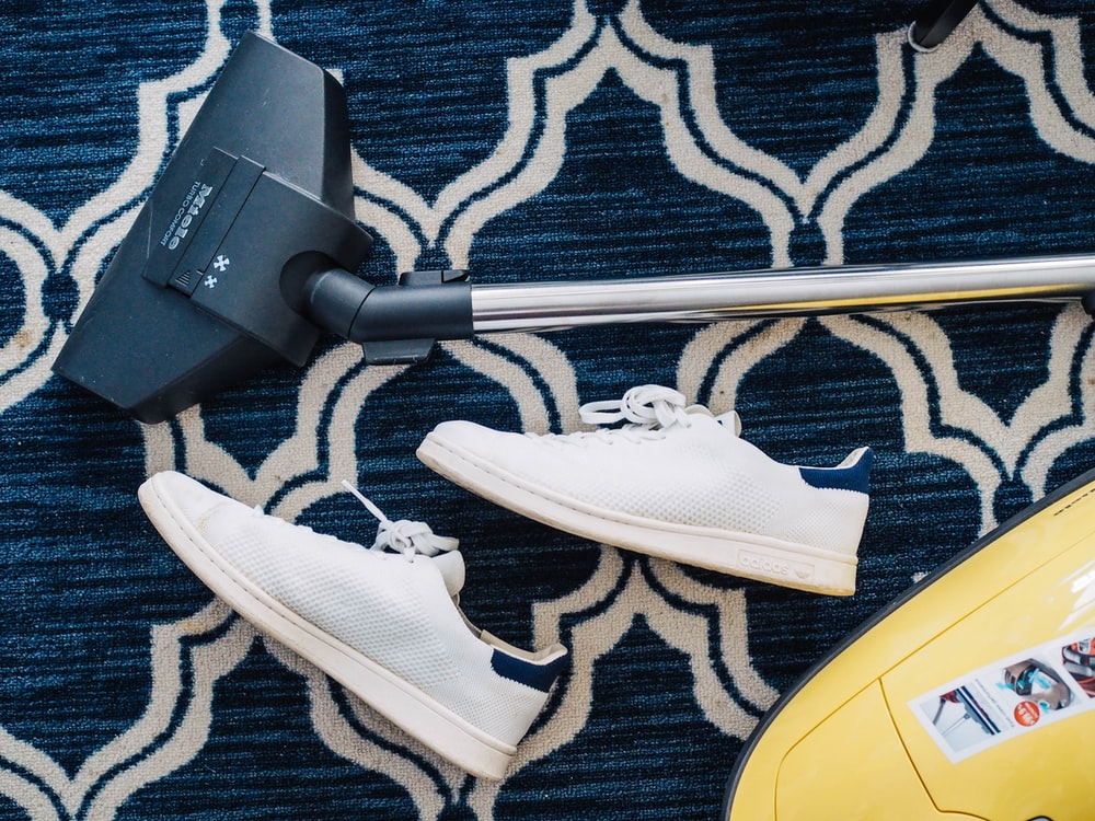 pair of white sneakers beside vacuum cleaner