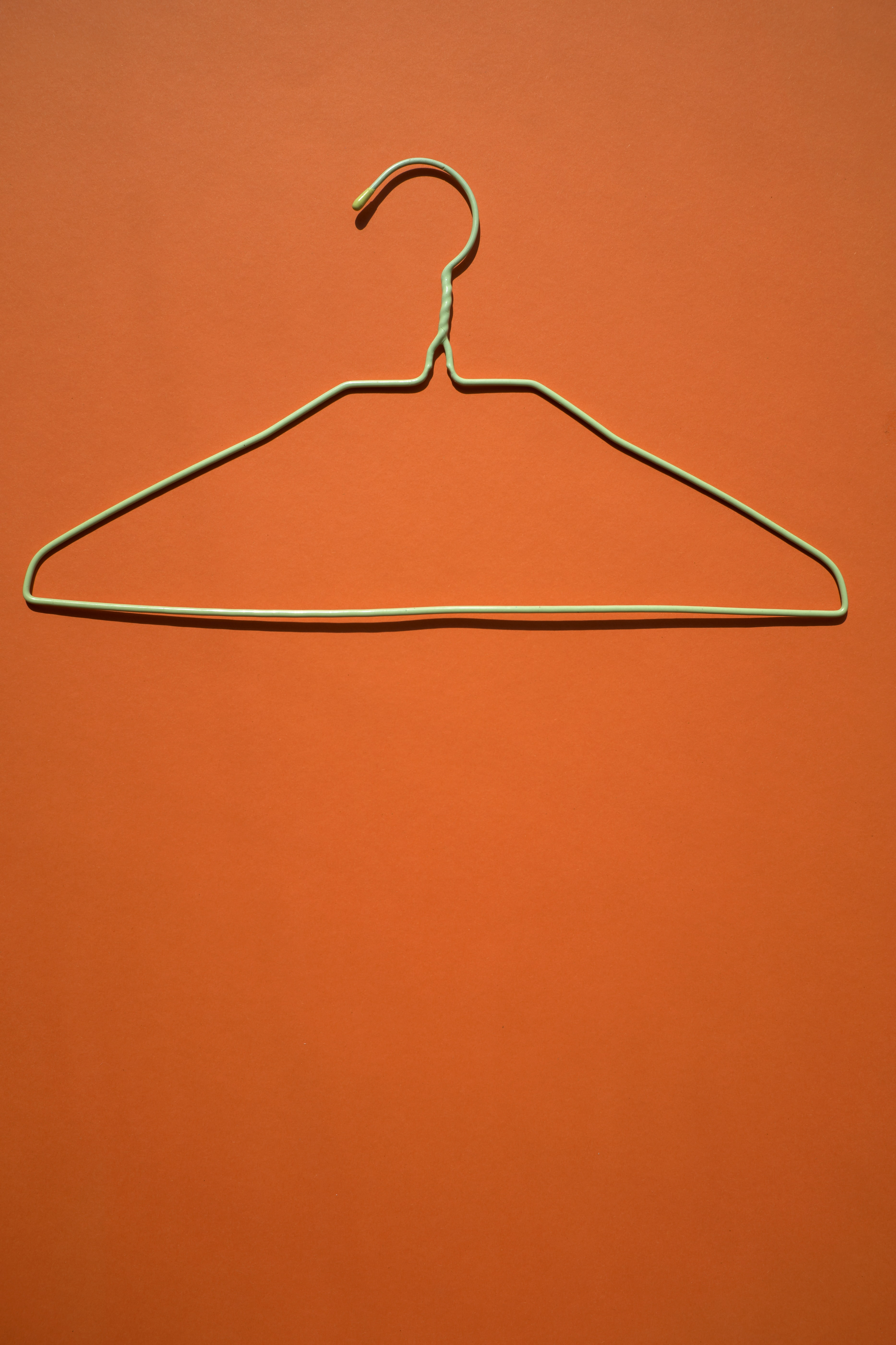 white clothes hanger on orange flooring