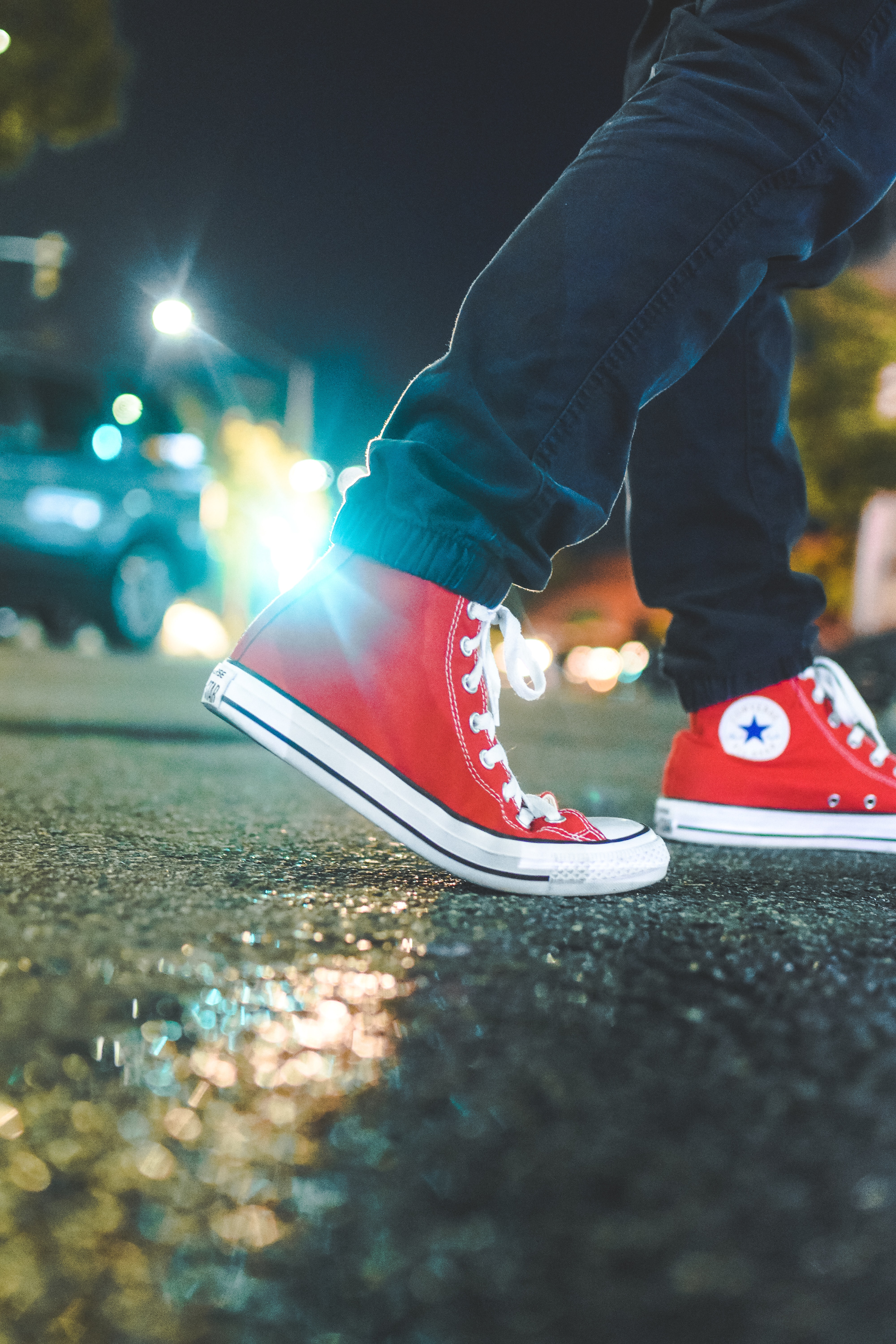worm's eye view photo of person wearing pair of red Converse All Star sneakers