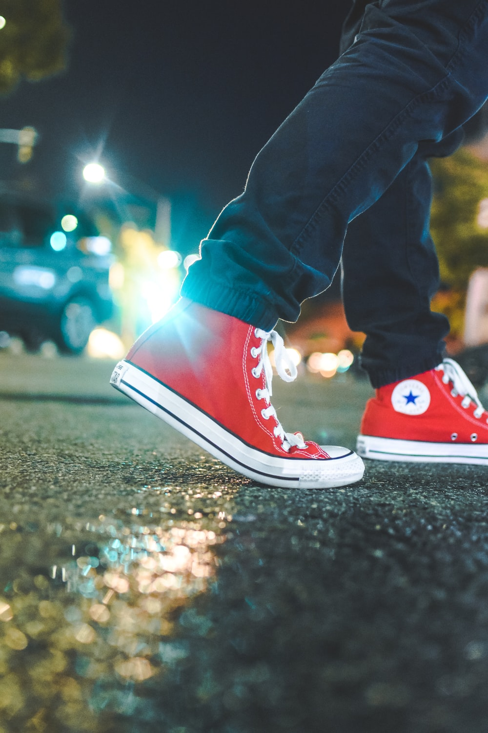 3cd040377 worm's eye view photo of person wearing pair of red Converse All Star  sneakers